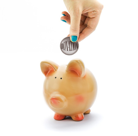 Hand depositing coin with Donation text in piggy bank photo