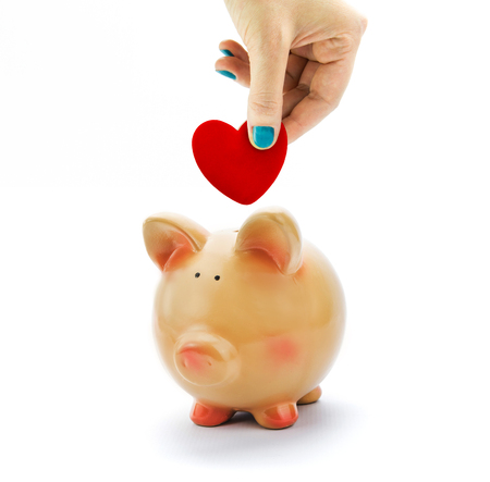 Hand deposit red heart in piggy bank isolated photo