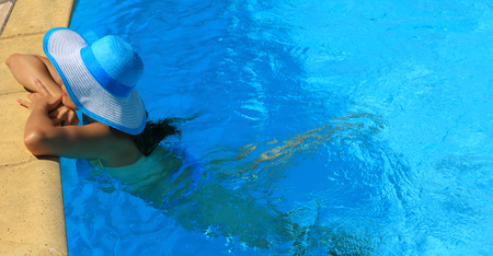 Young lady with white blue hat by the poolside Stock Photo
