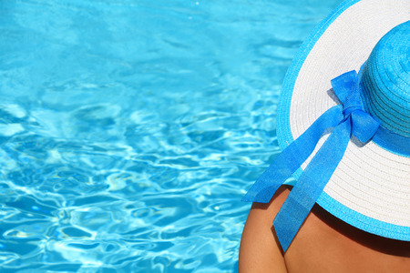 Young lady with white blue hat by the poolside photo