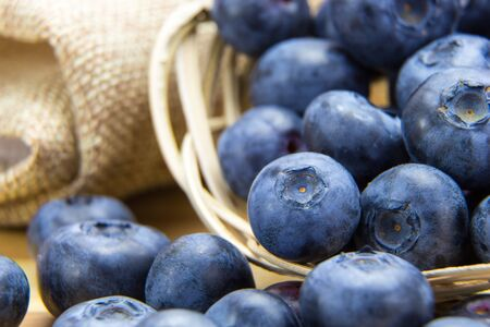 Macro shot of fresh ripe blueberries in wicker basket  Stock Photo