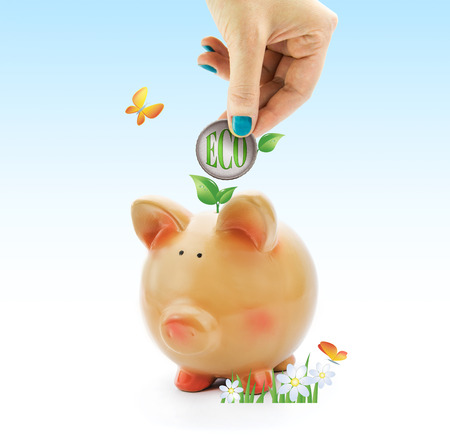 Hand depositing a coin with eco green text and leaves in piggy bank