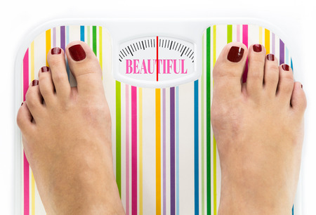 Feet on bathroom scale with word Beautiful on dial