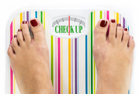 Feet on bathroom scale with words Check up on dial Stock Photo