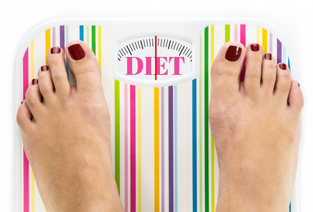 Feet on bathroom scale with word Diet on dial photo