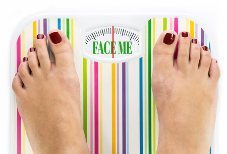 Feet on bathroom scale with words Face me on dial Stock Photo