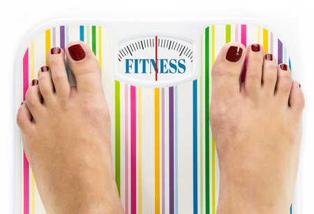 Feet on bathroom scale with word Fitness on dial Stock Photo