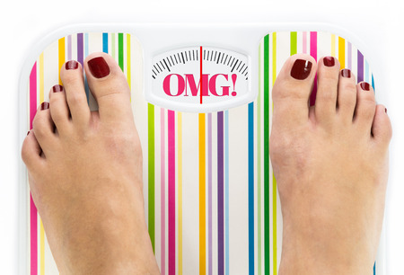 Feet on bathroom scale with word OMG on dial