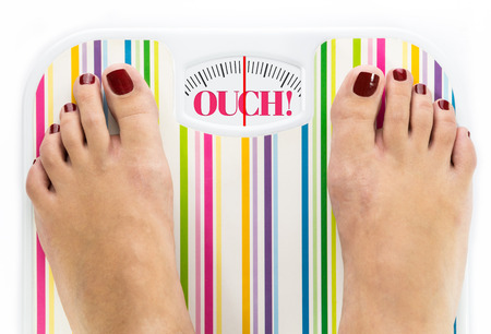 Feet on bathroom scale with word Ouch on dial Stock Photo