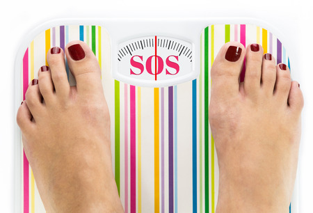Feet on bathroom scale with word SOS on dial