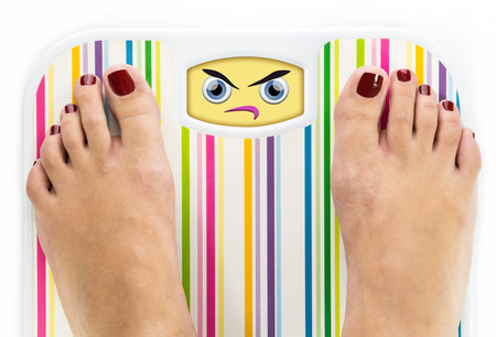 Feet on bathroom scale with angry cute face on dial Stock Photo