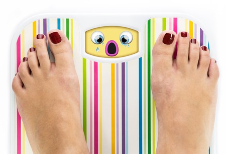 Feet on bathroom scale with crying cute face on dial photo