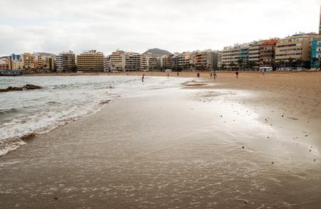 Wet sandy beach with cityscape Las Palmas de Gran Canaria Stock Photo