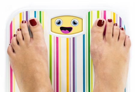 Feet on bathroom scale with laughing cute face on dial photo