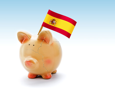 Piggy bank with cracks and national flag of Spain photo