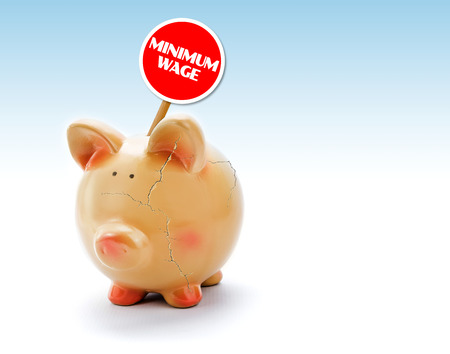 """Broken piggy bank with cracks and \""""Minimum Wage\"""" tag Stock Photo"""