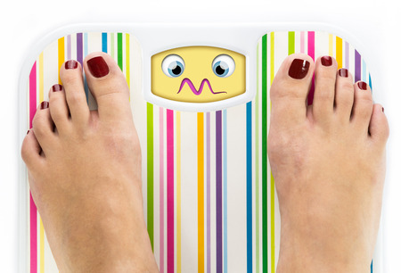 overwhelmed: Feet on bathroom scale with overwhelmed cute face on dial
