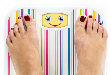 Feet on bathroom scale with smiling cute face on dial photo