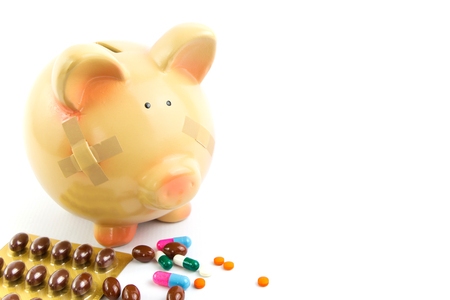 Piggy bank with medical patches and pills isolated on white photo