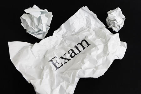 Crumpled paper sheet with word Exam isolated on black Stock Photo