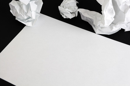 Blank paper sheet and crumpled papper balls isolated Stock Photo