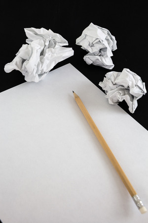 Blank paper sheet with pencil and crumpled papper balls isolated