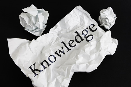 Crumpled paper sheet with word Knowledge isolated on black