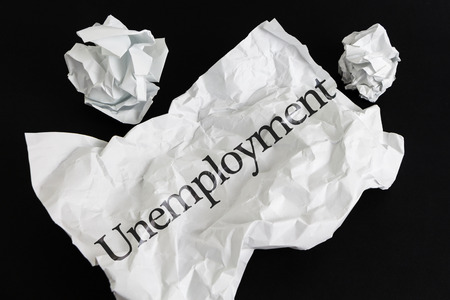 Crumpled paper sheet with word Unemployment isolated on black Stock Photo