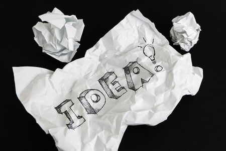 Crumpled paper sheet with word Idea isolated on black