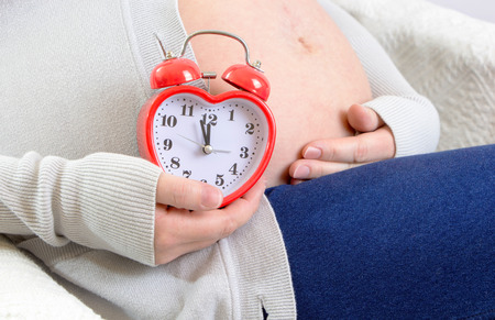 Pregnant womans belly with alarm clock in shape of a heart