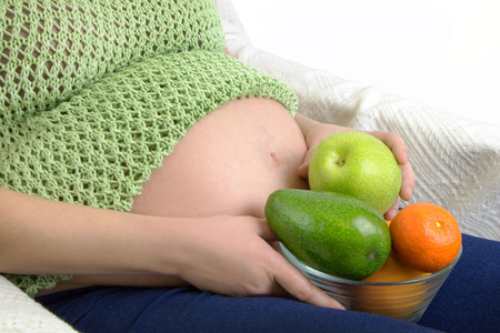 Pregnant woman with bowl of fruits and vegetables