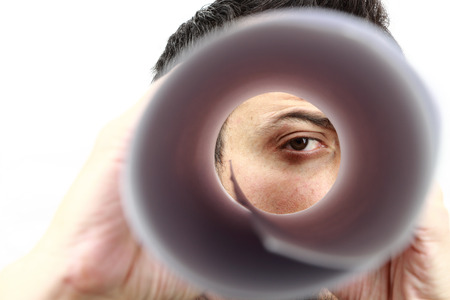 Male face looking in the rolled paper like a spyglass