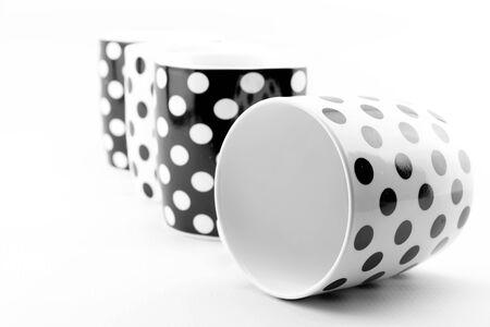 tea mug: Black and white polka dots mugs isolated on white background Stock Photo