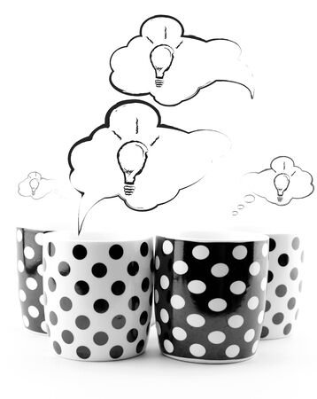 Coffee mugs with speech bubbles and light bulbs isolated on white
