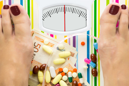 pill: Bathroom scale with pills and money, dial with lines no numbers