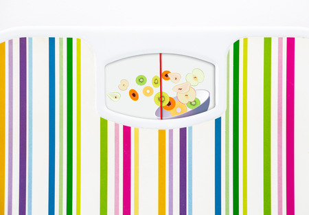 Bathroom scale with bowl of fruits on dial with no numbers