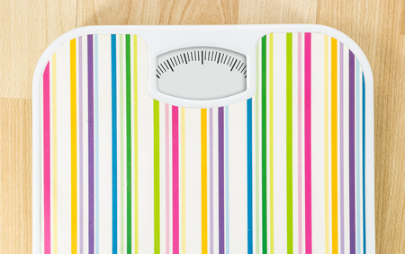 Bathroom scale with clean dial with lines no numbers on wooden floor Stock Photo