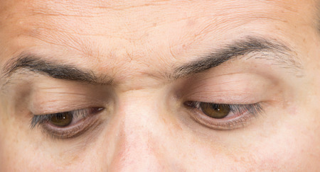 eyes looking down: Upper part of males face closeup on eyes looking down Stock Photo