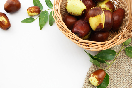 jujube fruits: Jujube fruits in wicker basket closeup, on white background Stock Photo