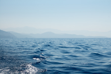 mountains and sky: Seascape with distant mountains, sky and wavy sea water