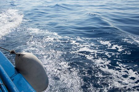 fender: Seascape with water trail from boat with white fender Stock Photo