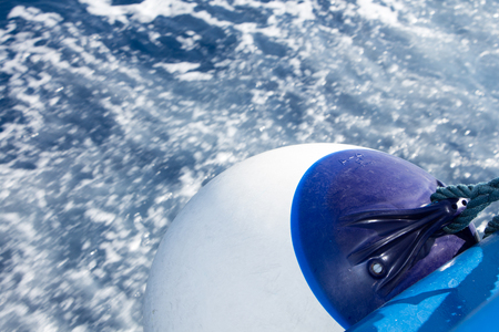 fender: Seascape with water trail from boat with focus on white ball fender Stock Photo