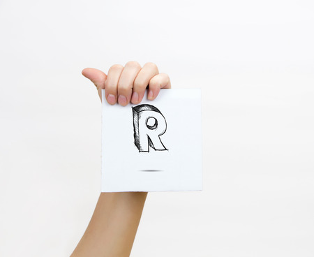 piece of paper: Hand holding a piece of paper with sketchy capital letter  R, isolated on white.