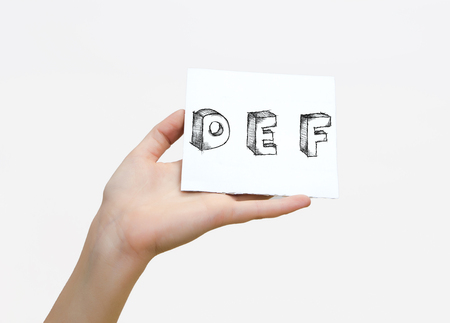 e white: Hand holding a piece of paper with sketchy capital letters  D E F, isolated on white.