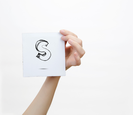 piece of paper: Hand holding a piece of paper with sketchy capital letter  S, isolated on white. Stock Photo