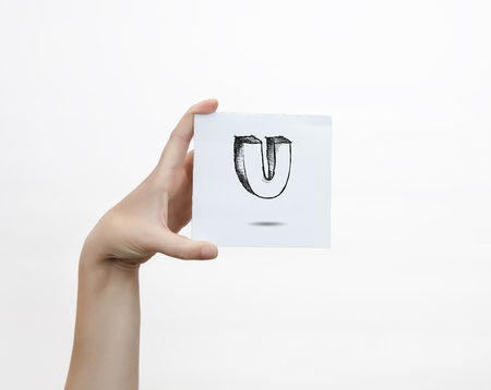 piece of paper: Hand holding a piece of paper with sketchy capital letter  U, isolated on white.