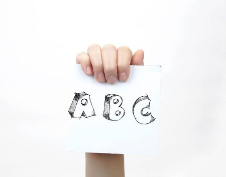 piece of paper: Hand holding a piece of paper with sketchy capital letters ABC, isolated on white.