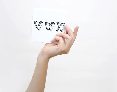 piece of paper: Hand holding a piece of paper with sketchy capital letters V W X, isolated on white.