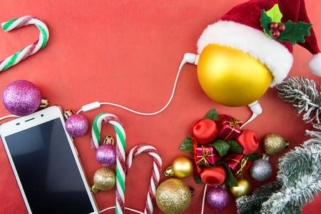 Kerstmisbal met de hoed van de Kerstman en smartphone met oortelefoons, op rood met exemplaar-ruimte