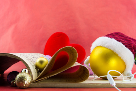 music notation: Christmas ball with Santas hat and earphones, music notation book with pages shaping heart, on red background.